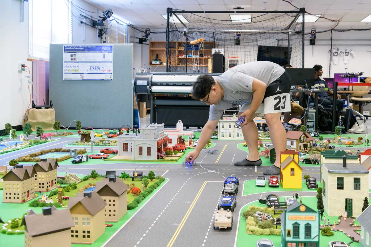 Yiming Wan places an item in UD's Mini Smart City