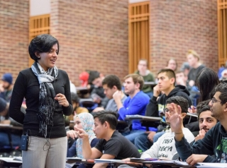 Arthi Jayaraman stands before a group of students.