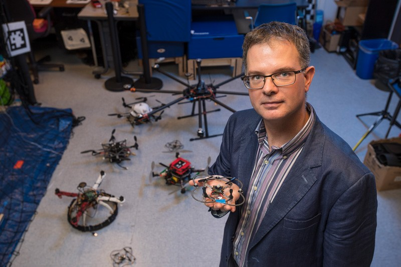 Bert Tanner is pictured in his laboratory. He is holding a tiny drone, and several drones surround him.