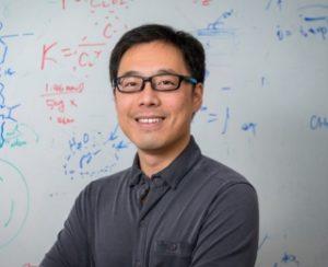 Bingjun Xu is pictured in front of a white board.