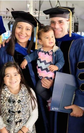 Parents in graduation robes holding children