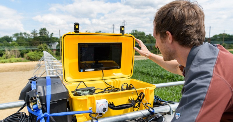 Adam Stager, doctoral student in mechanical engineering, monitors crop data from atop the irrigation system in the outdoor lab at UD's Newark farm during the summer.