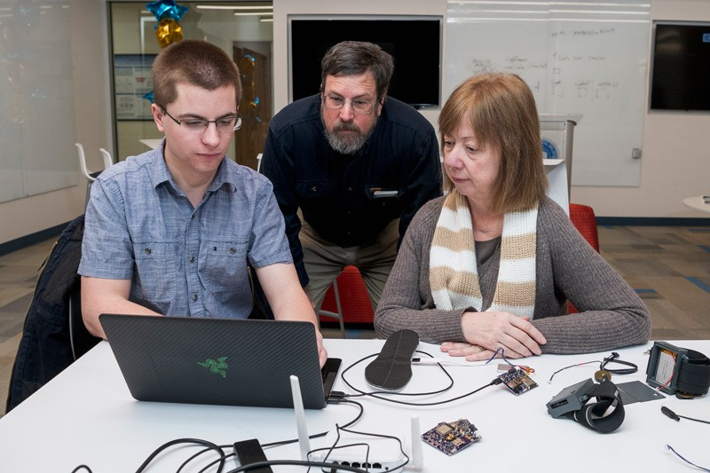 UD junior Theodore Fleck (far left) demonstrates the web interface he helped build to remotely control the device's vibrating motors and log the data collected by sensors for Prof. Scott Jones and Ingrid Pretzer-Aboff, senior nurse scientist at Virginia Commonwealth University.