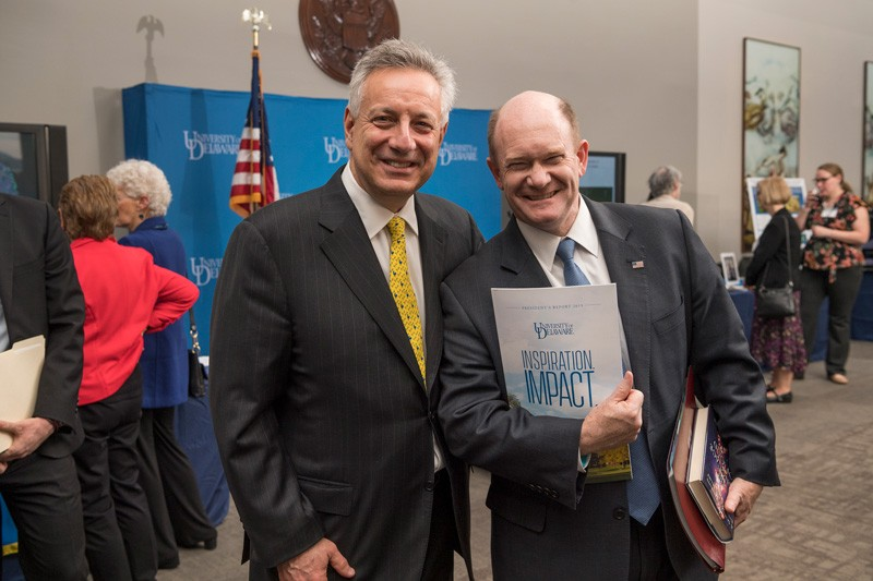 U.S. Sen. Chris Coons (right) has a degree in chemistry and is a powerful advocate for University of Delaware research. Here he shows off his new copy of UD President Dennis Assanis' annual report.