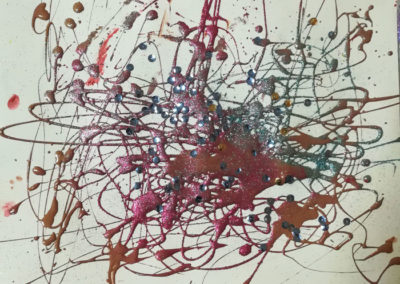 Artwork created by students at Serviam Girl's Academy using a pendulum and paint