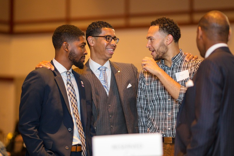 Wali Rushdan II (second from left) speaks with students during the 2019 Students of Distinction dinner.