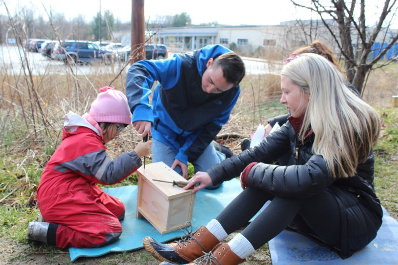 A child works on a birdhouse as part of a program in which College of Education and Human Development students and faculty collaborate with College of Engineering students and faculty to help children learn about birds.