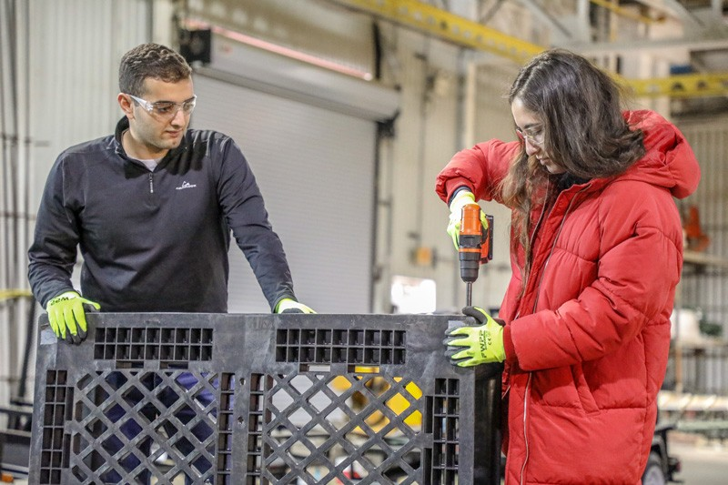 Lucas Attia (left) and Phoebe Dowden drill together pallets for the Early Learning Center's outdoor learning environment re-design.