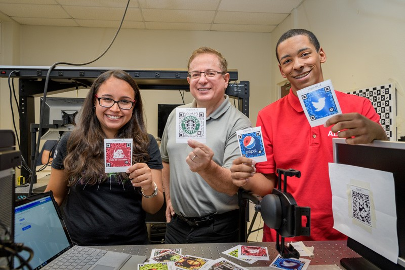 From left to right, UD doctoral student Karelia Pena; Gonzalo Arce, Charles Black Evans Professor of Electrical and Computer Engineering; and David Miller, a student at Mount Pleasant High School in Wilmington, Delaware, show the QR codes they have studied using sophisticated optical equipment in a laboratory in UD's Evans Hall.