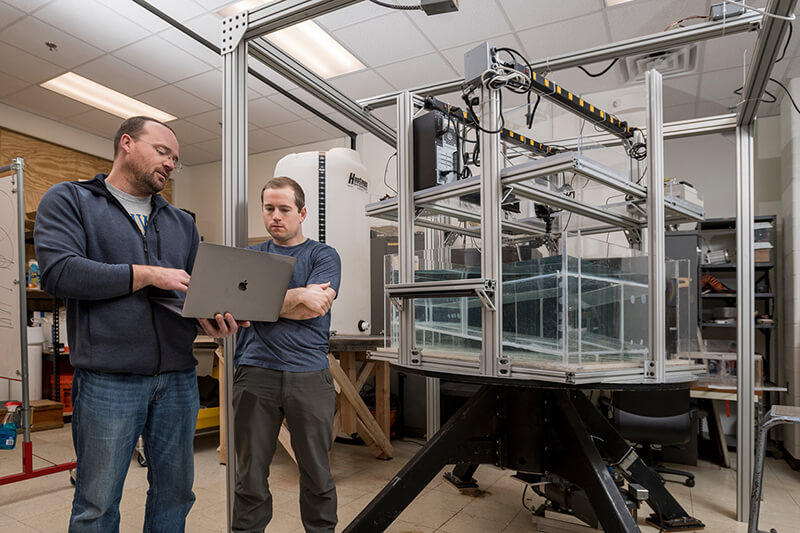 Joe Kuehl and graduate student Charles McMahon work with a rotating tank so help determine the ocean current loop in the Golf of Mexico and the South China Sea.