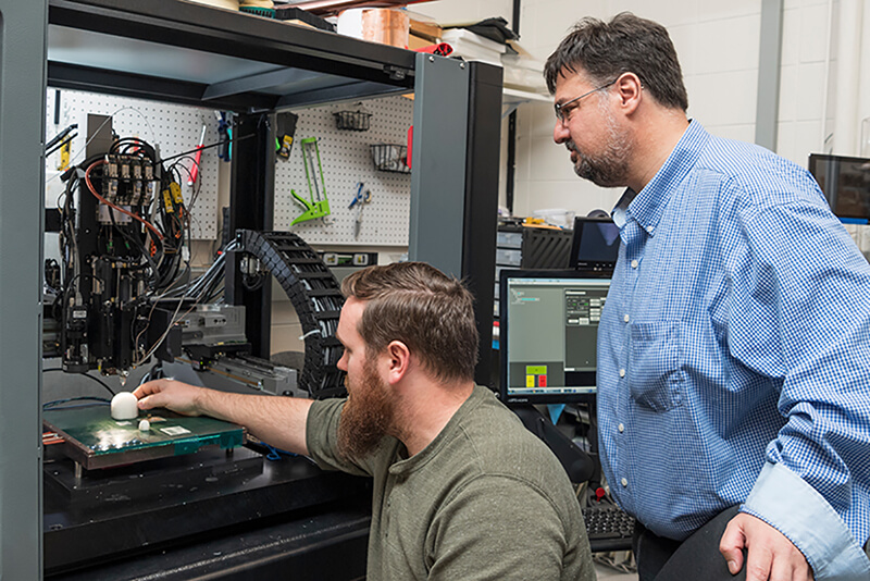 Mark Mirotznik and grad student Zachary Larimore work with the new 3-D printer in the Electrical & Computer Engineering Lab in Evans Hall, May 7th, 2018.
