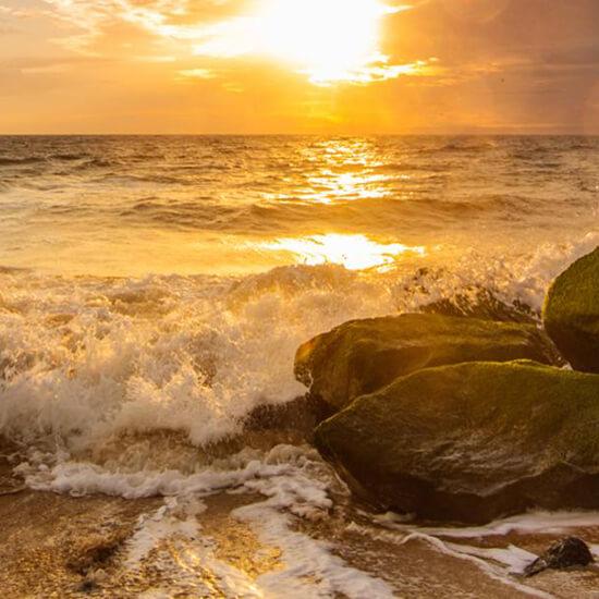 Waves crash on rocks on beach at Cape Henlopen State Park