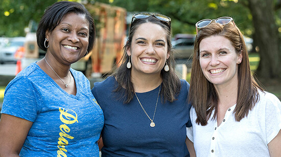 Three women on campus with one wearing a Delaware T-Shirt